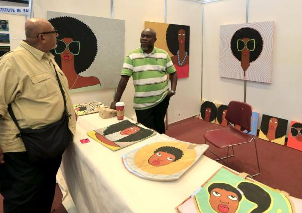 Kenyan artist Michael Soi (R) stands next to his paintings at the Kenya Art Fair 2015 exhibition at the Sarit Centre in Kenya's capital Nairobi November 14, 2015. REUTERS/Noor Khamis