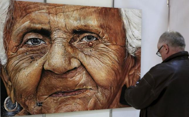 An art admirer looks at one of the paintings at the Kenya Art Fair 2015 exhibition at the Sarit Centre in Kenya's capital Nairobi November 14, 2015. REUTERS/Noor Khamis