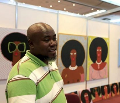 Kenyan artist Michael Soi stands next to his paintings at the Kenya Art Fair 2015 exhibition at the Sarit Centre in Kenya's capital Nairobi November 14, 2015.  REUTERS/Noor Khamis